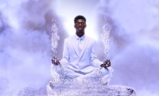 Lil Nas X sits in a white suit on a pathway made of ice floating in the skies