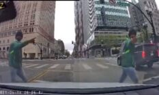 The view of a street crossing from a vehicle's dash cam, showing a man in a green hoodie and blue jeans walk past