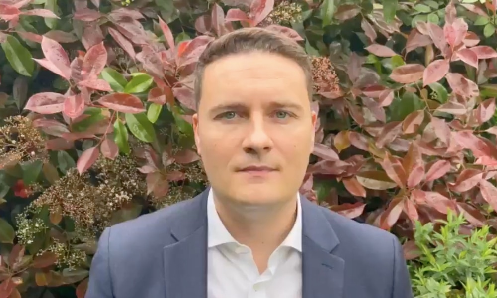 Wes Streeting wearing a shirt and blazer in front of a bush
