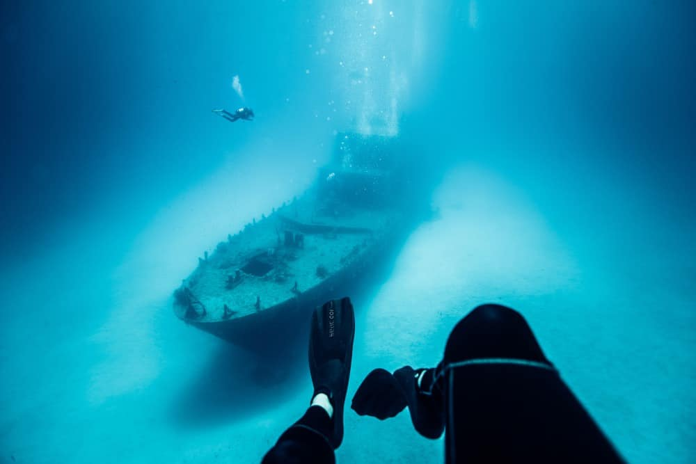 Picture of a person's feet underwater with shipwreck visible