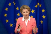 President of the European Commission Ursula von der Leyen holds a press conference in a pink zip-up jacket agains the EU flag