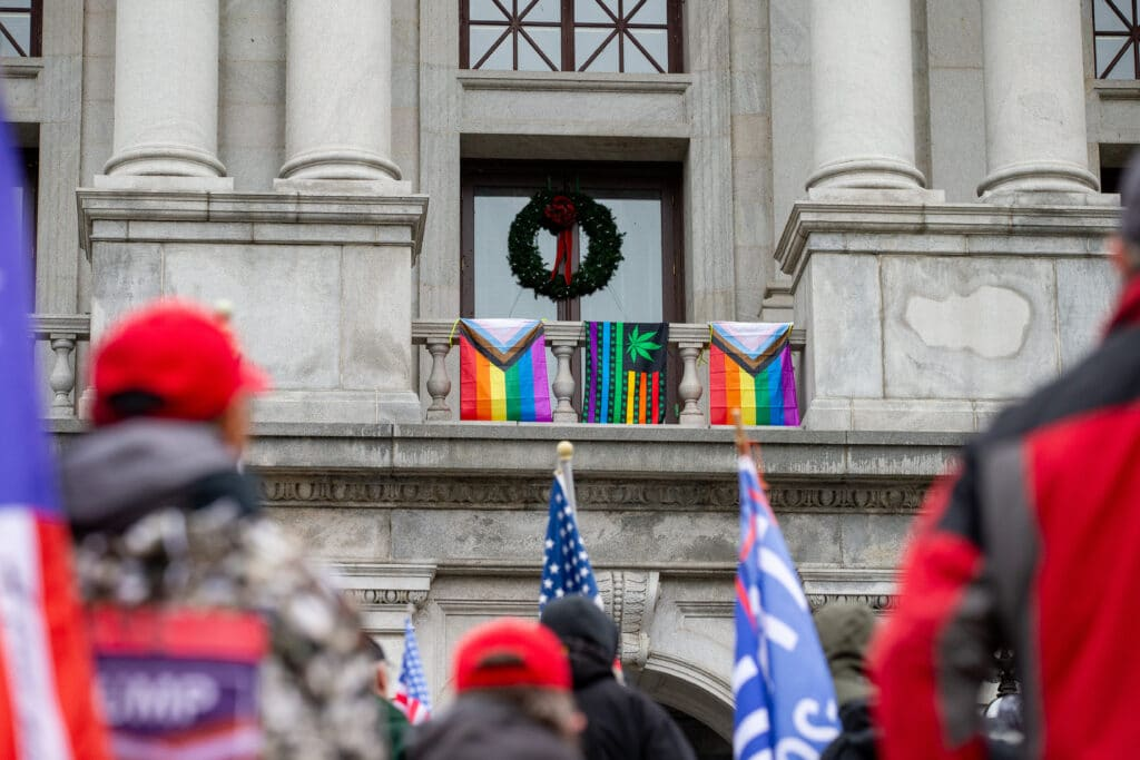 Flags are seen hanging from the balcony outside of Pennsylvania lieutenant governor John Fetterman's office as pro-Trump demonstrators rally below, Supporters of President Donald Trump urged legislators to decertify the election