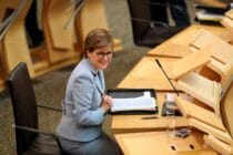 Nicola Sturgeon sits down in Holyrood in a blue pant suit