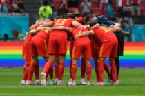 Denmark players form a circle in front of a rainbow advert during the UEFA Euro 2020 Championship Round of 16 match between Wales and Denmark