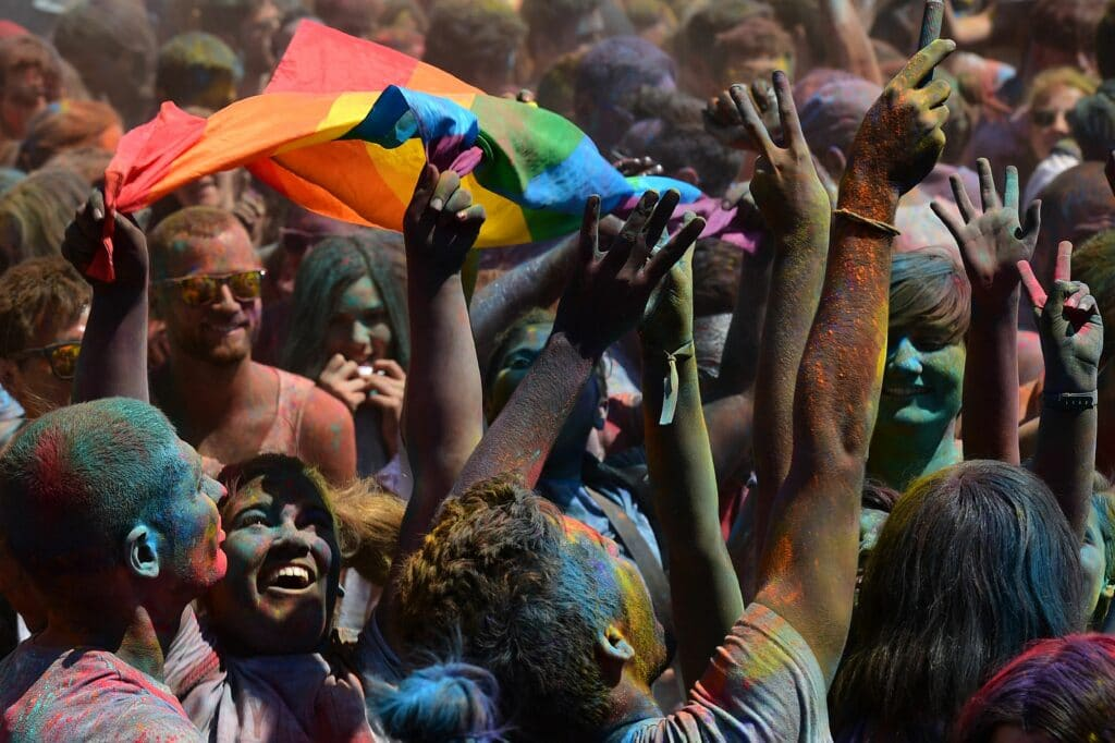 A woman brandishes a Rainbow flag during a Holi Party before the Gay Pride Parade in Barcelona