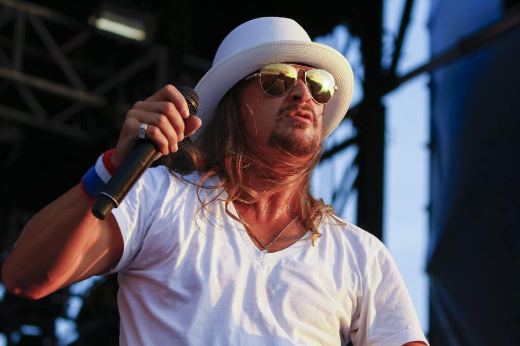Kid Rock performs in a white v-neck and white fedora