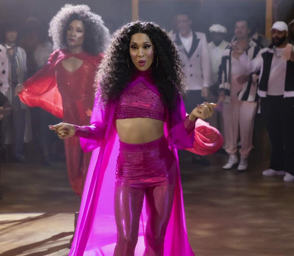 Mj Rodriguez as Blanca performing in the ballroom, wearing a pink crop top, legginga and cape