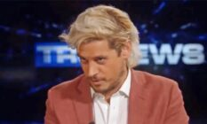 Milo Yiannopoulos looks down while wearing a shirt and blazer
