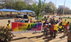 """Holding a banner that says """"Liberty, Justice Four All"""", Malawi Pride-goers walk along a street"""