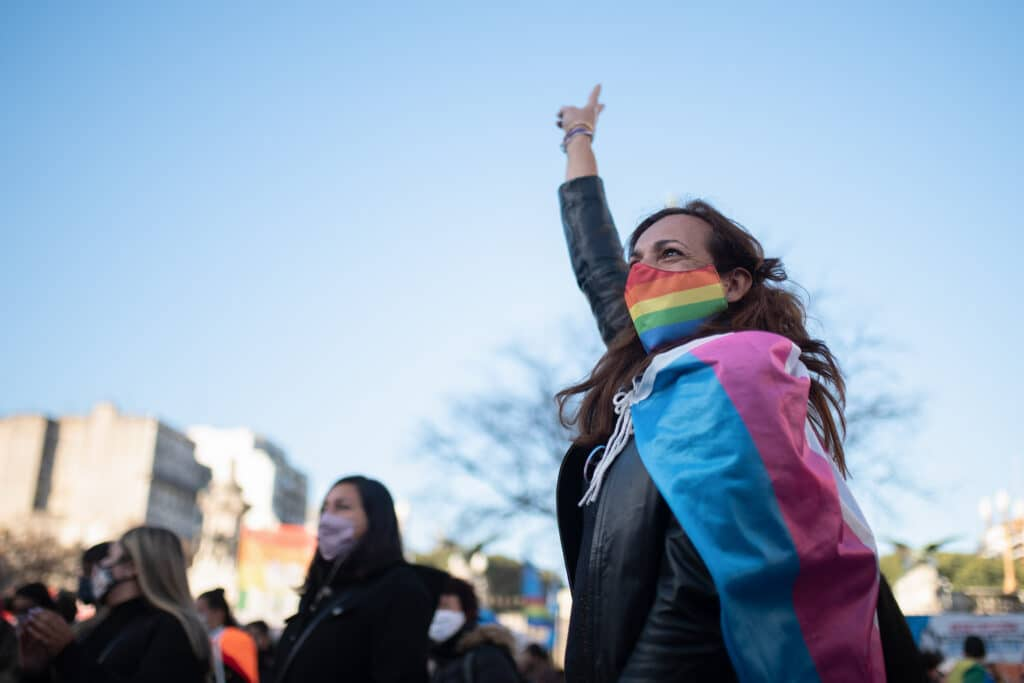 A person in a rainbow face mask punches their fist in the air