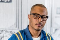 T.I. looks to the camera in a blue bomber jacket and black glasses