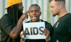 """DaBaby holds up a sign with the word """"AIDS"""" on it"""