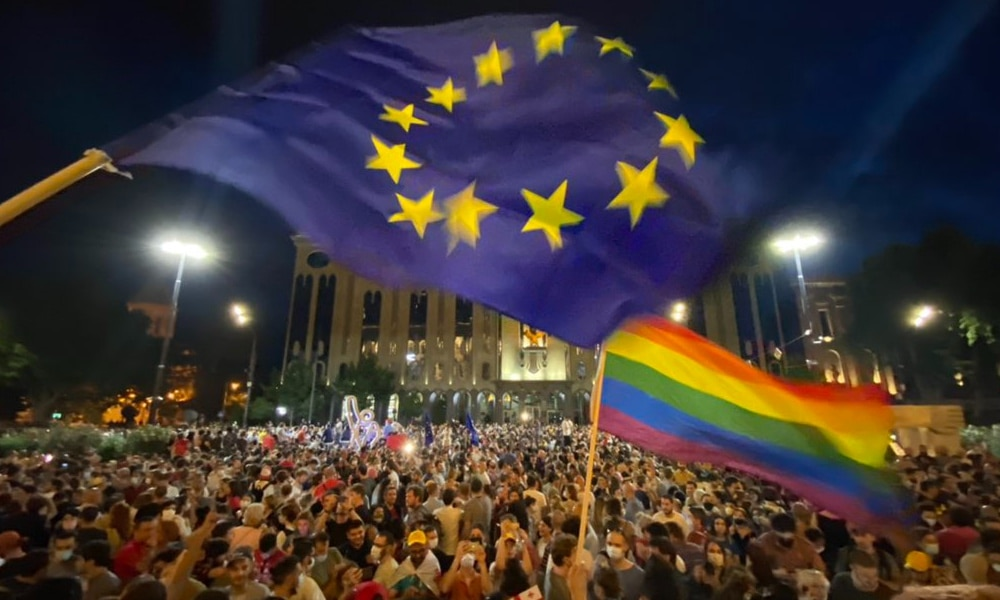 Thousands in front of the Georgian Parliament Building waving LGBT+ Pride flags