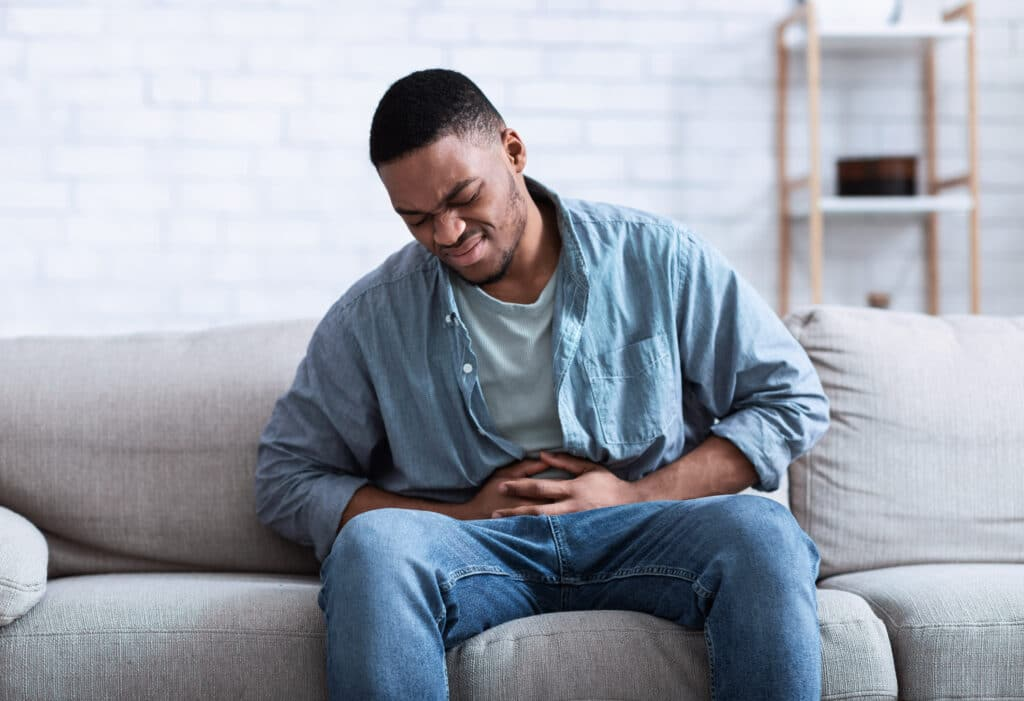 A Black man having a painful stomach ache, caressing his tummy