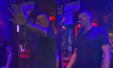 A bouncer tries to stop his photograph being taken at a dimly-lit bar