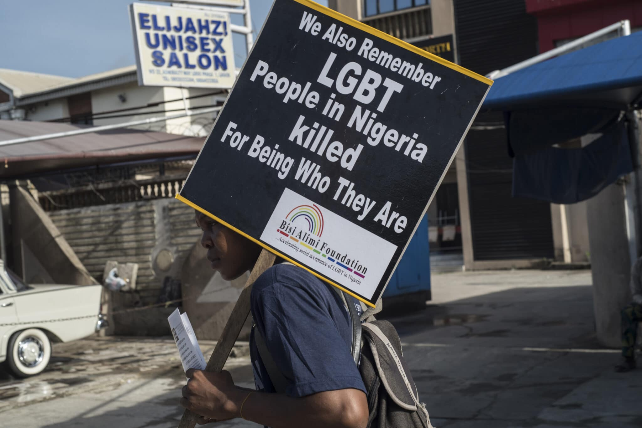 A young man holds a sign remembering the murders of LGBT+ people in Nigeria