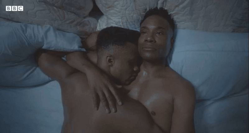 Ricky and Pray in bed, naked, Pray is leaning on Pray's chest, their arms around each other in a post-coital embrace