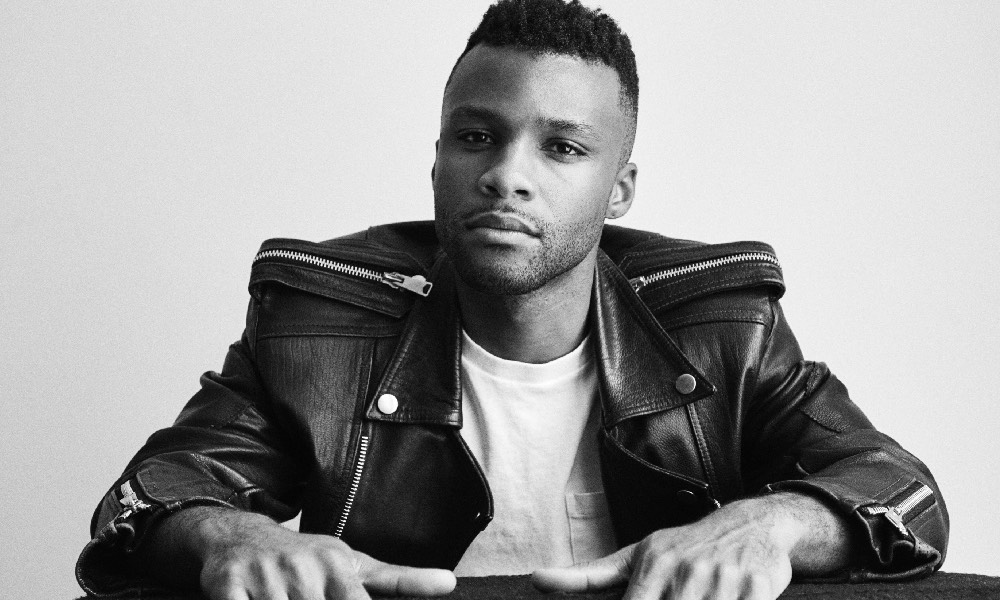 Black and white photo of Dyllón Burnside in a black leather jacket and white t-shirt, sat at a table