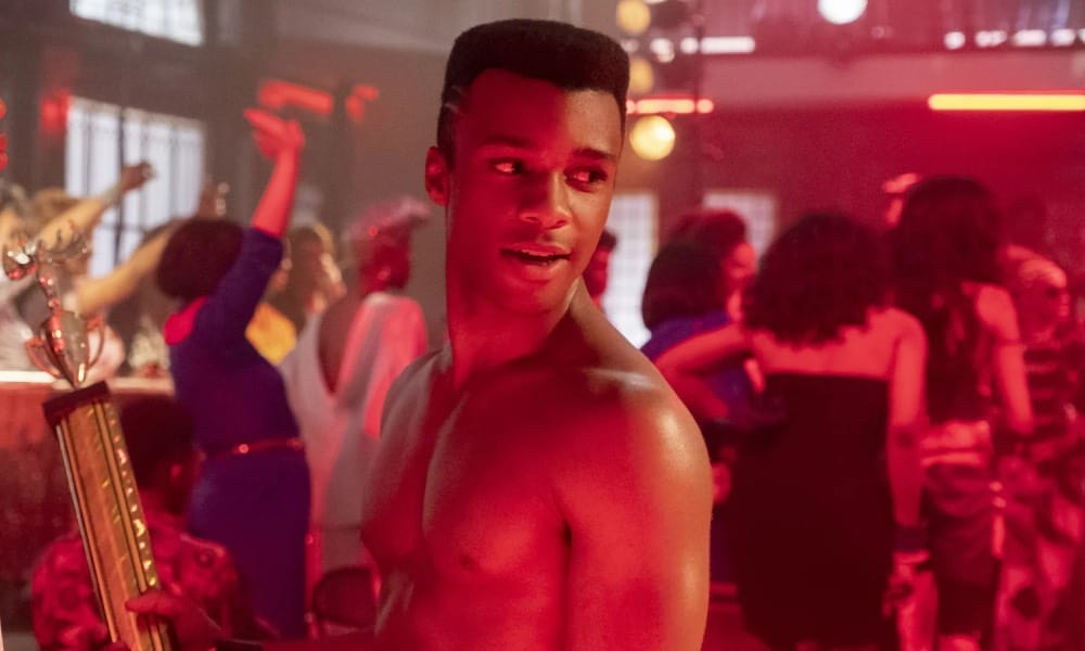 Dyllón Burnside as Ricky in Pose, topless, holding a trophy