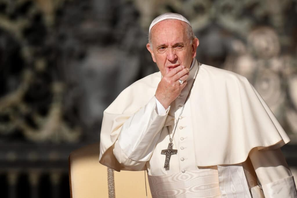 Pope Francis looks on with his hand over his face