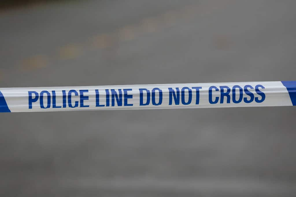A police tape that reads 'police line do not cross'