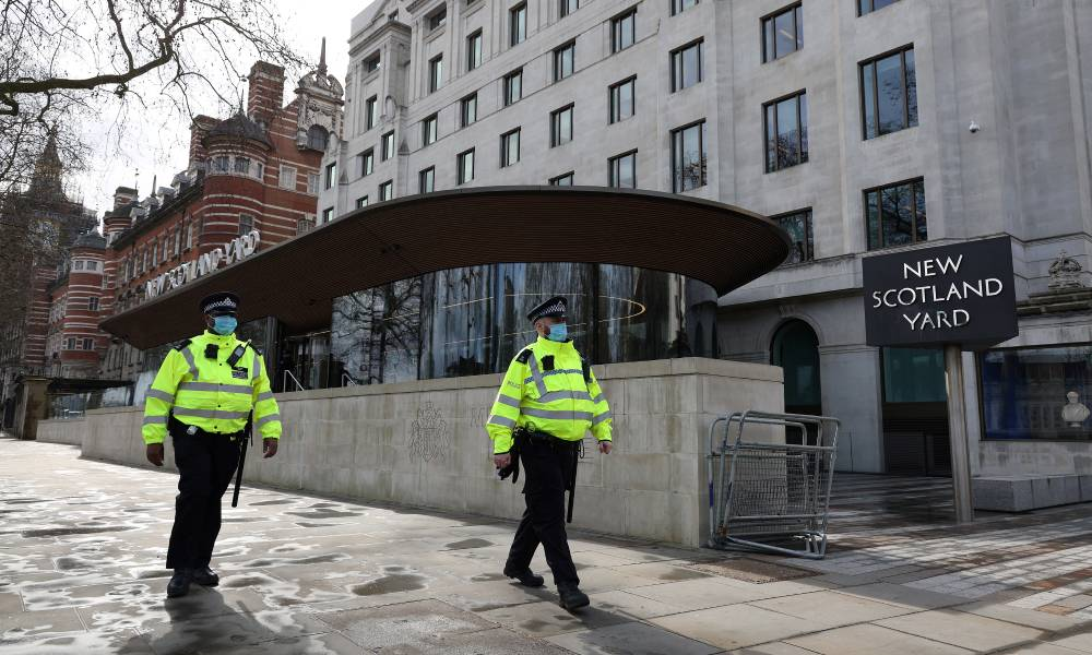 Police officers wearing face coverings due to Covid-19 walk past New Scotland Yard, the headquarters of the Metropolitan Police Service