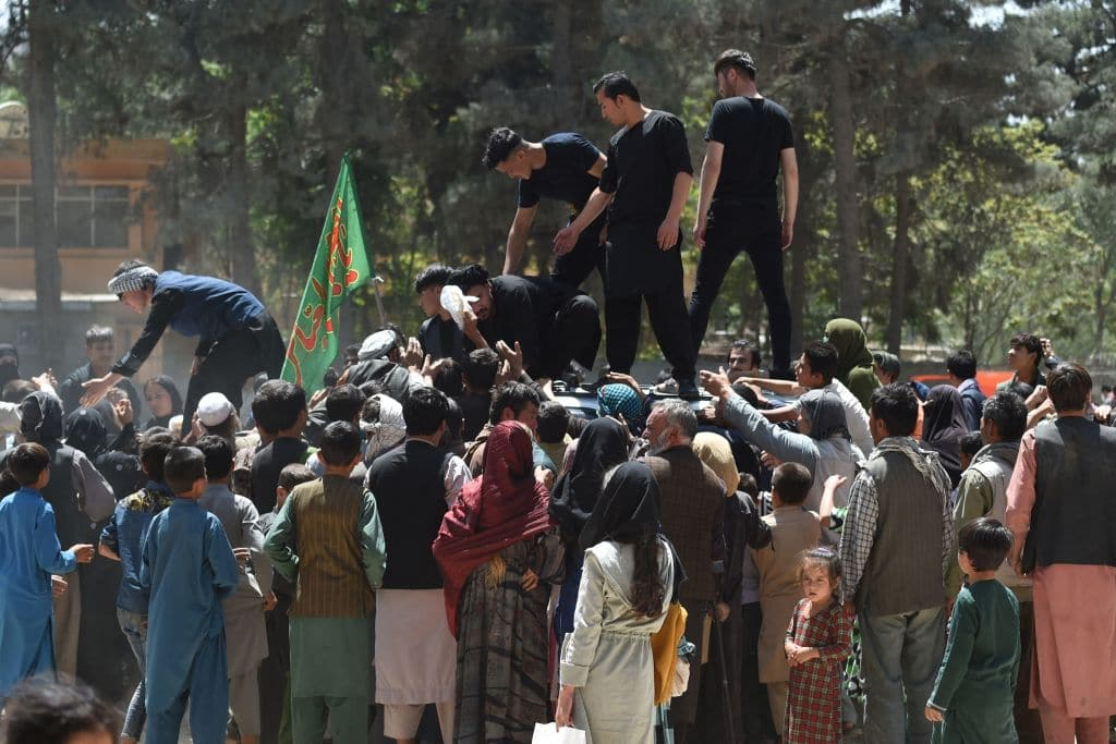 Internally displaced Afghan people, who fled from the northern province due to battle between Taliban and Afghan security forces, gather to receive free food being distributed by Shiite men at Shahr-e-Naw Park in Kabul on August 13, 2021.