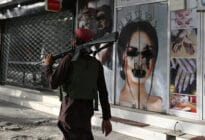 A Taliban fighter walks past a beauty salon with images of women defaced.