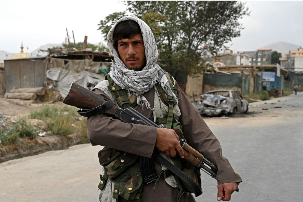 A Taliban fighter stands guard near a damaged car after multiple rockets were fired in Kabul on August 30, 2021.