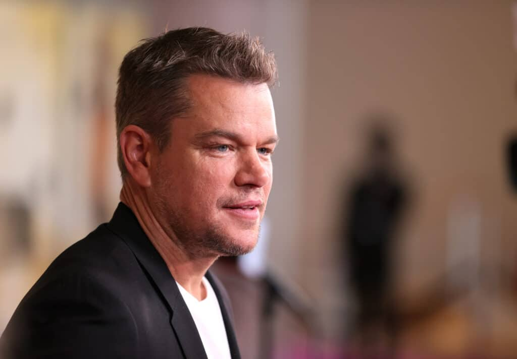 Matt Damon from the side in a white tee and black blazer