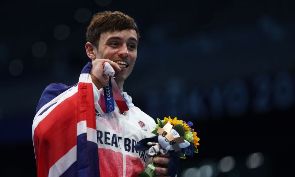 Tom Daley posing with his gold medal
