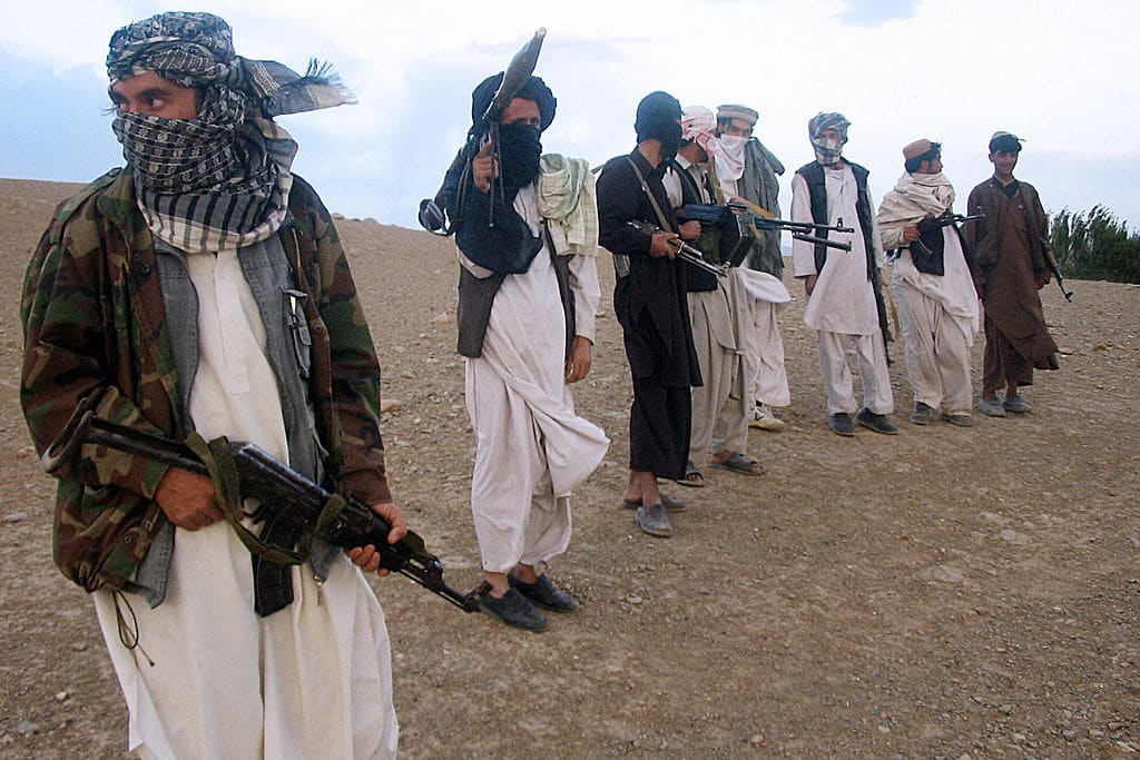 Members of the Taliban stand holding weapons