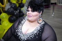 Stacy Layne Matthews poses to the camera in a black dress