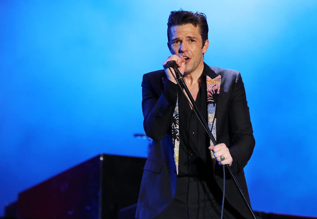 Brandon Flowers of The Killers performs in a black blazer