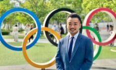 Trans activist and former fencer Fumino Sugiyama smiling in front of olympic rings