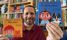 Lawrence Schimel holds Russian translations of children's books 'Early One Morning' and 'Bedtime, Not Playtime!'