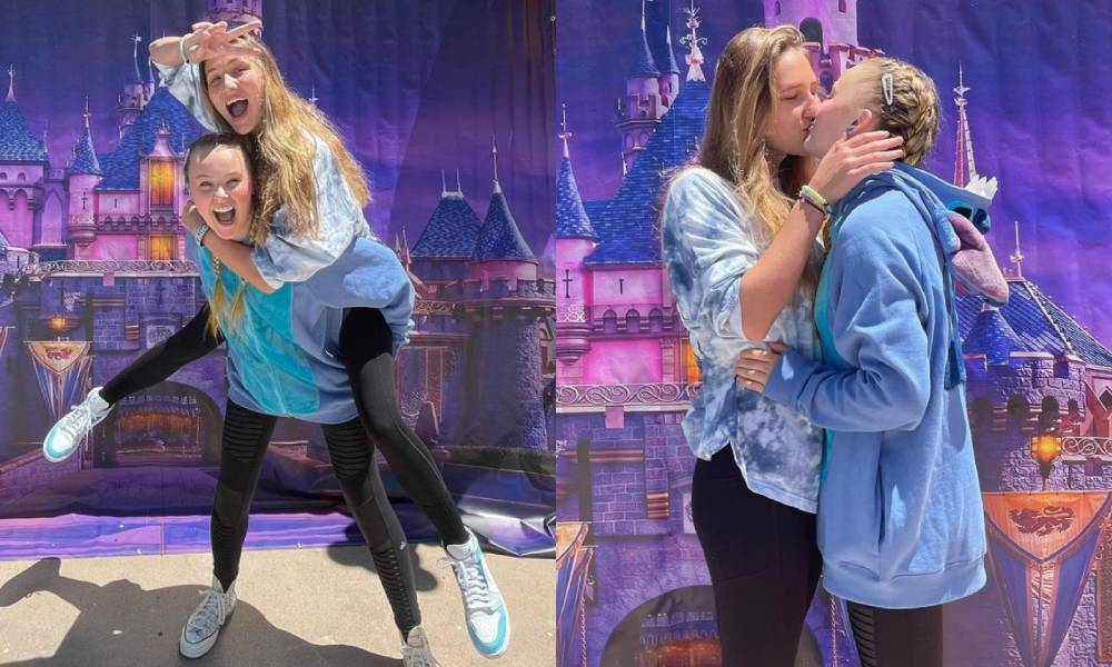 JoJo Siwa and Kylie Prew are seen having fun and sharing a kiss in front of a Disney backdrop with colourful Mickey Mouse balloons