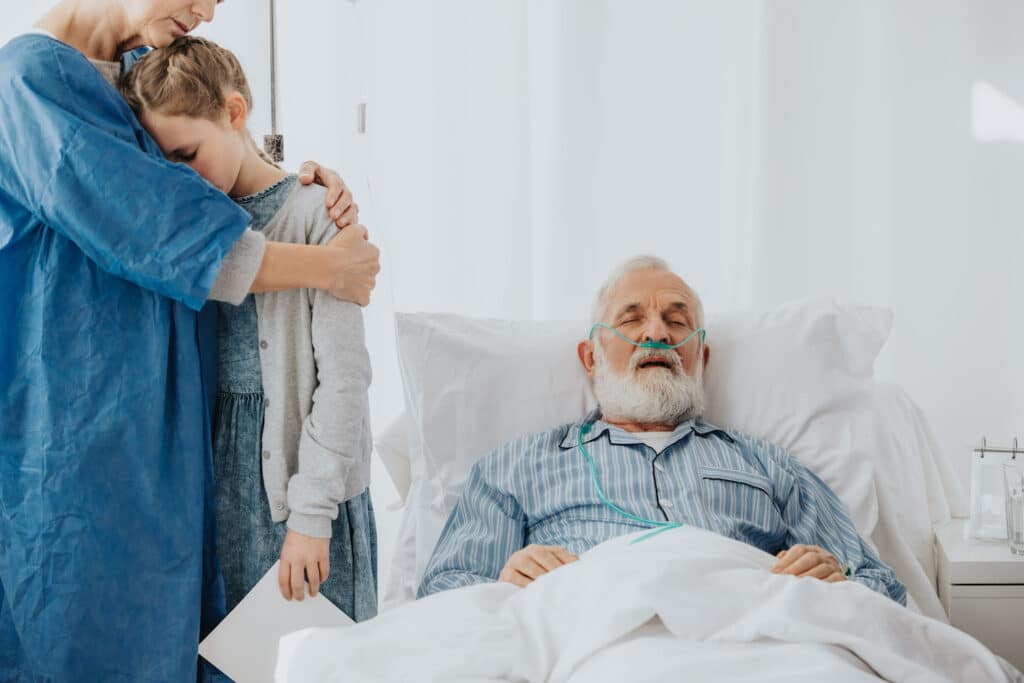 A family stands around their grandfather as he lies dying in a hospital bed