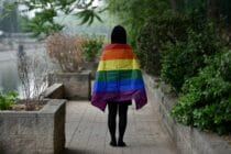 Student with rainbow flag draped over their shoulders, photographer from behind, in Beijing, China