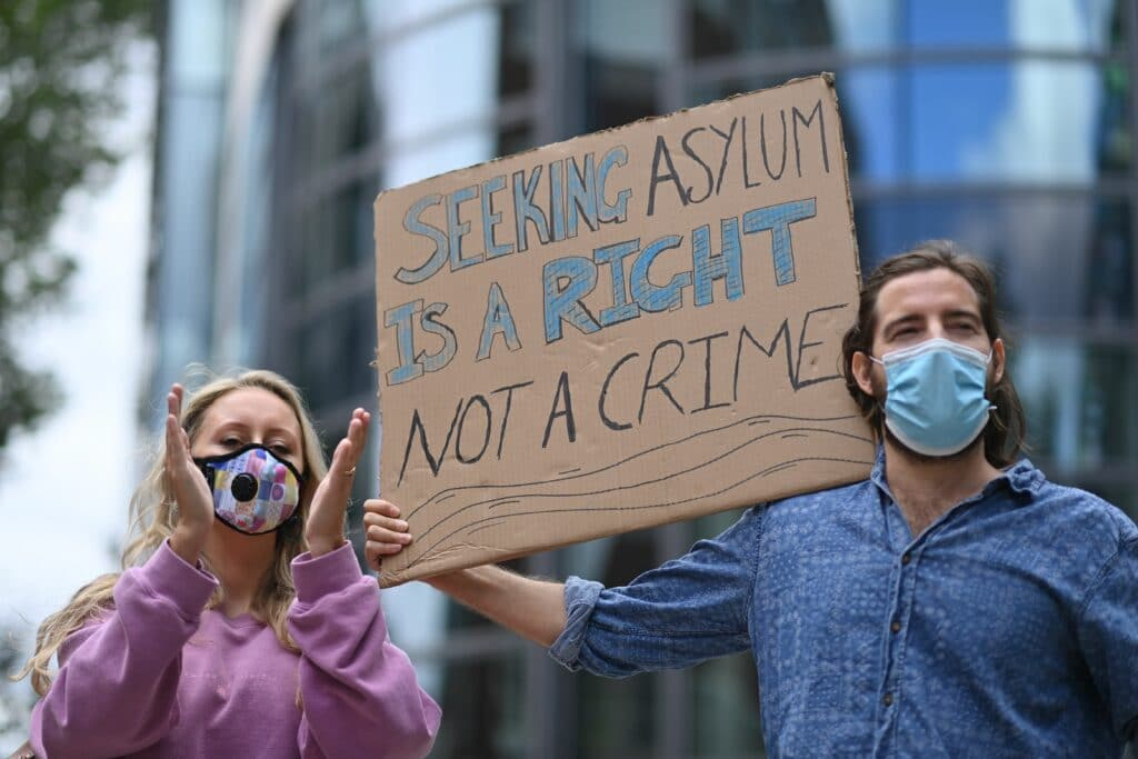 Protesters outside the Home Office holding a sign that reads: Seeking asylum is a right not a crime