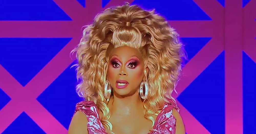 RuPaul in full drag, wearing a pink dress and blonde wig