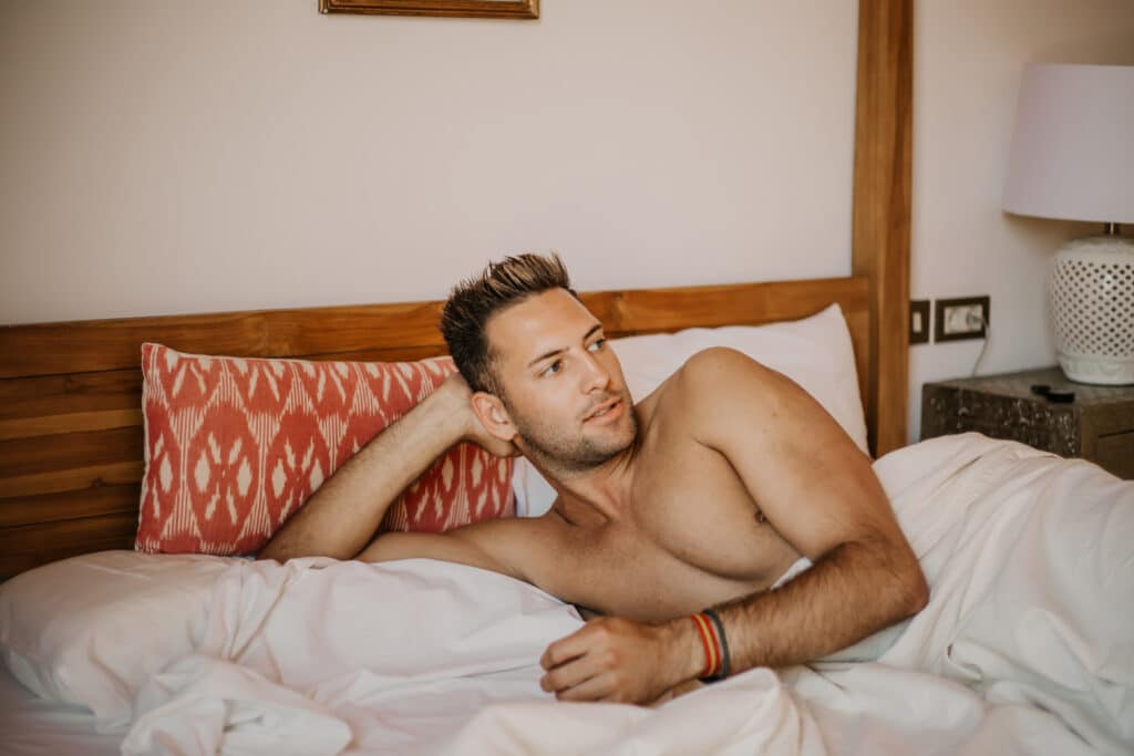Shirtless sexy male model lying alone on his bed in his bedroom.Carefree guy enjoying new day.