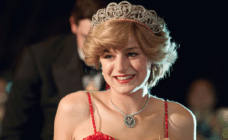 Emma Corrin as PRincess Diana in a red strappy dress, bouffant hair and tiara
