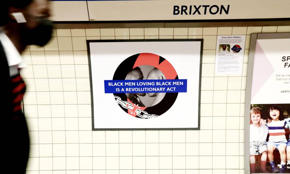 A person walks by the LGBT+ Pride roundel designed by Marc Thompson at Brixton station