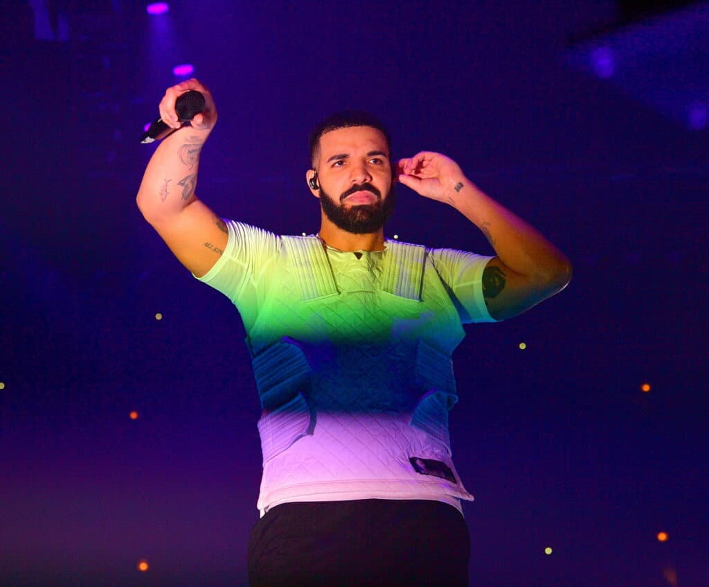 Drake with the colours of the rainbow shining on him