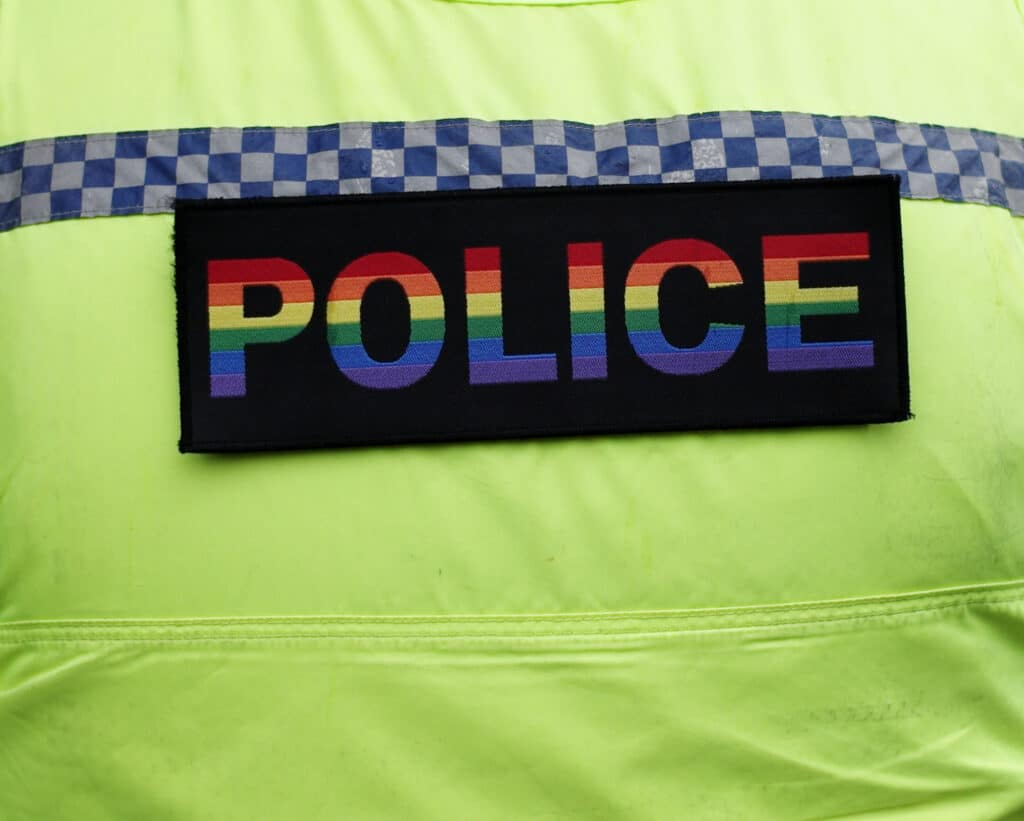A police officer wears a pride coloured police badge on his uniform