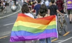 Two women hold the rainbow pride flag as they take part in the Queerschutz Now march in Berlin, Germany