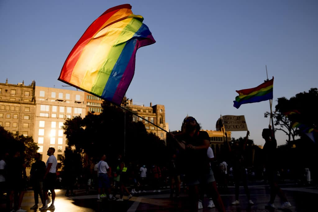 Thousands of people are demonstrating in Barcelona, Spain, waving a rainbow flag