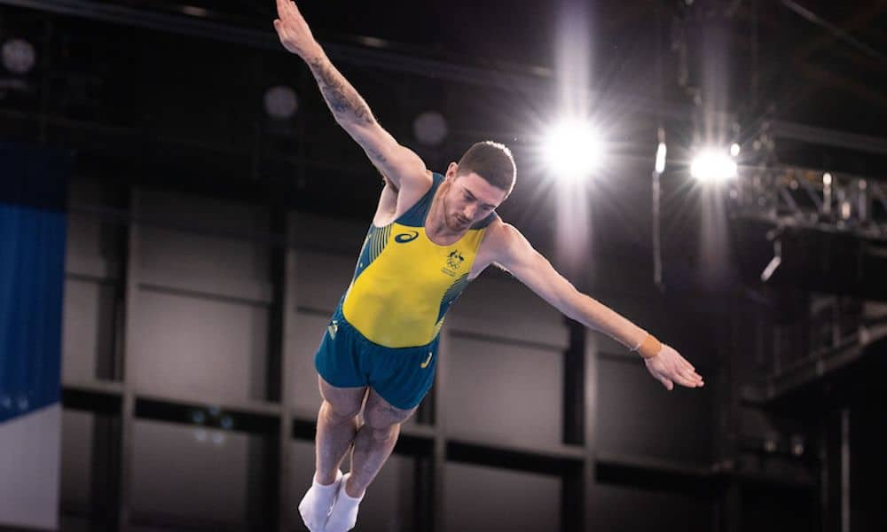 Dominic Clarke jumps with outstretched arms at the Tokyo 2020 Olympics