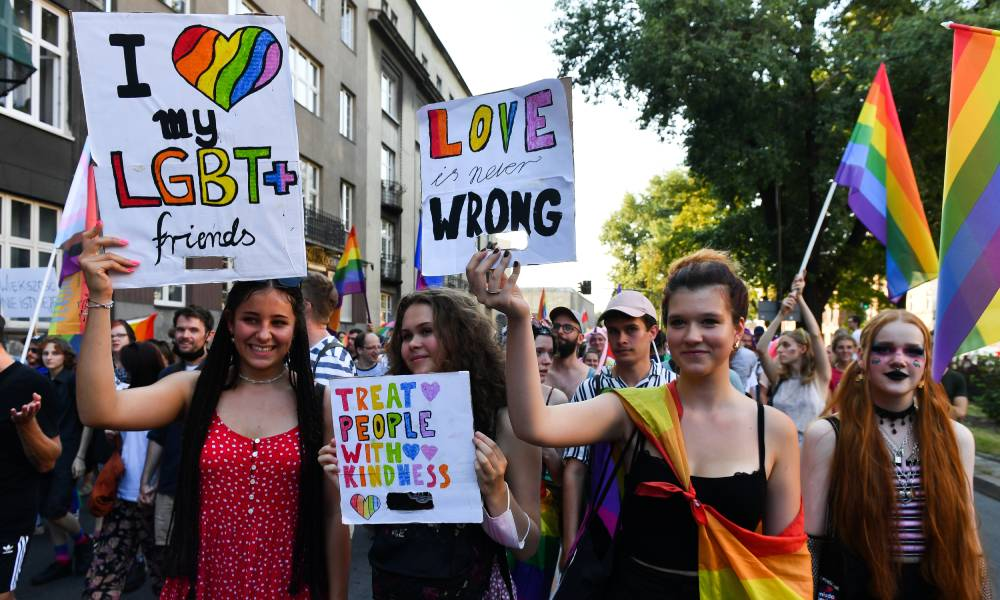 Participants holding placards supporting the LGBT+ community during Krakow Equality March in Poland